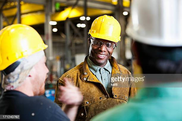 Multi-ethnic workers wearing hard hats, talking