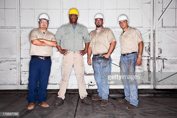Multi-ethnic workers wearing hardhats