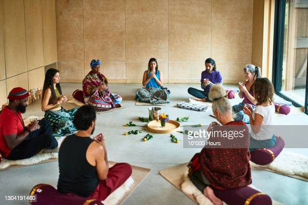 multi-ethnic yoga group drinking tea during ceremony - mid adult men stock pictures, royalty-free photos & images