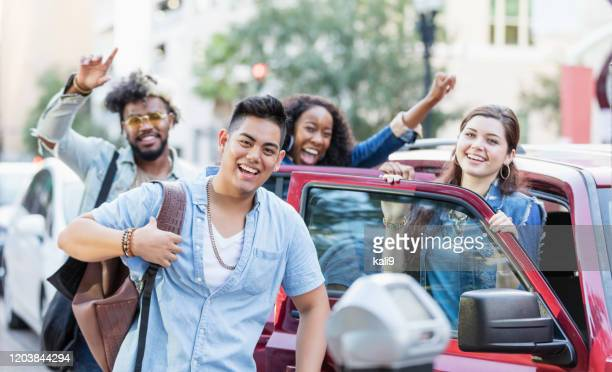 adultos jóvenes multiétnicos en la ciudad, entrando en coche estacionado - cuatro personas fotografías e imágenes de stock
