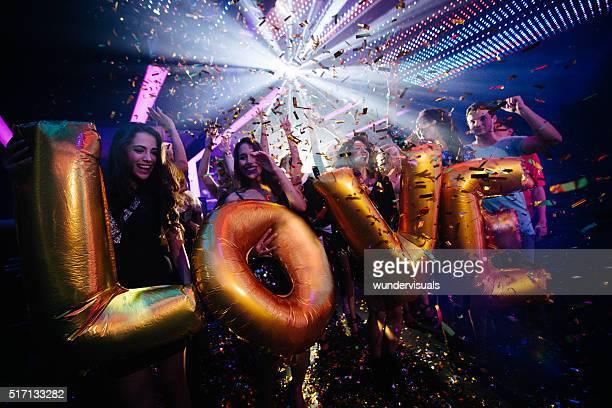 Multi ethniques jeunes amis célébrant un night-club avec des ballons de fête