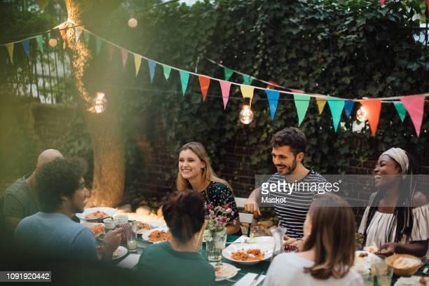 multi-ethnic young friends enjoying dinner at table during garden party - tischflächen aufnahme stock-fotos und bilder
