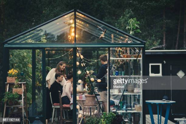 Multi-ethnic young friends enjoying garden dinner party in conservatory at back yard