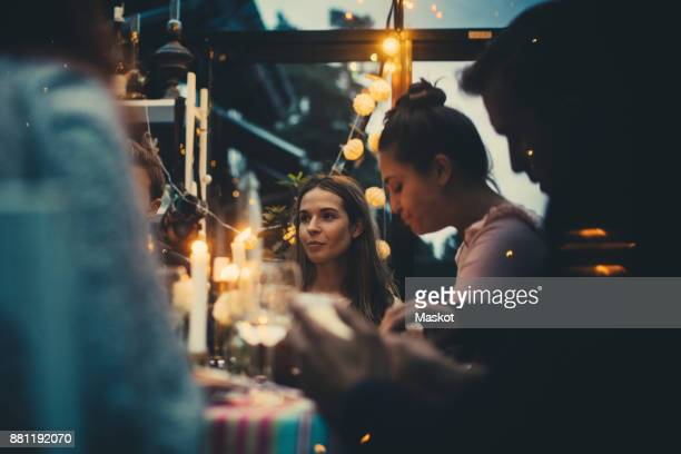 multi-ethnic young friends sitting in conservatory during dinner party - avondschemering stockfoto's en -beelden