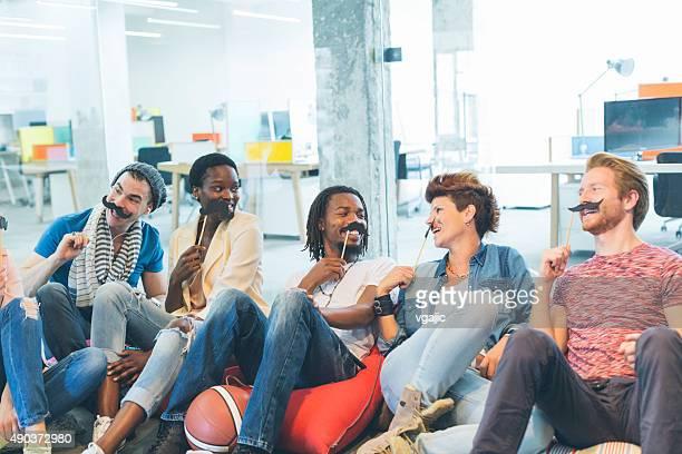 Multi-étnica jovens Celebrando Movember em seu escritório.