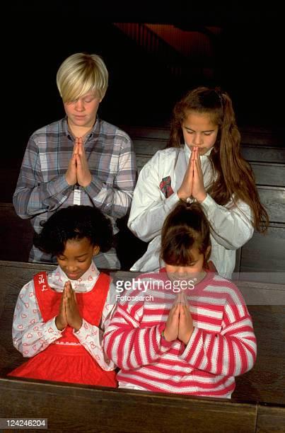 Multi-ethnic youths praying in church