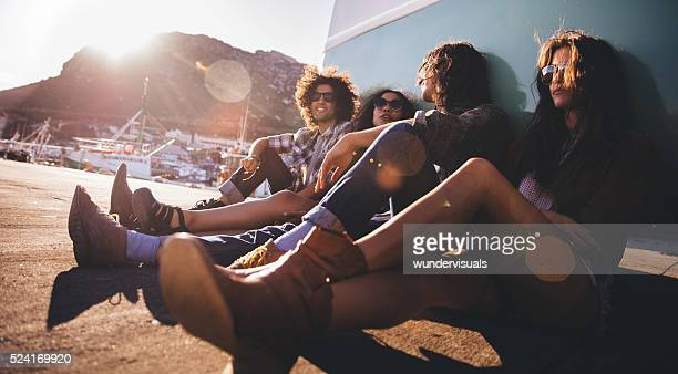 Multi-ethnical hipster friends resting out of their van at sunse