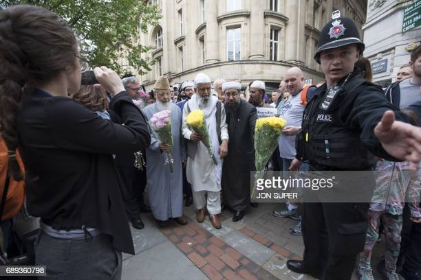 Multifaith leaders make their way to a gathering in St Ann's square to lay floral tributes for the victims of the Manchester bombing in Manchester on...