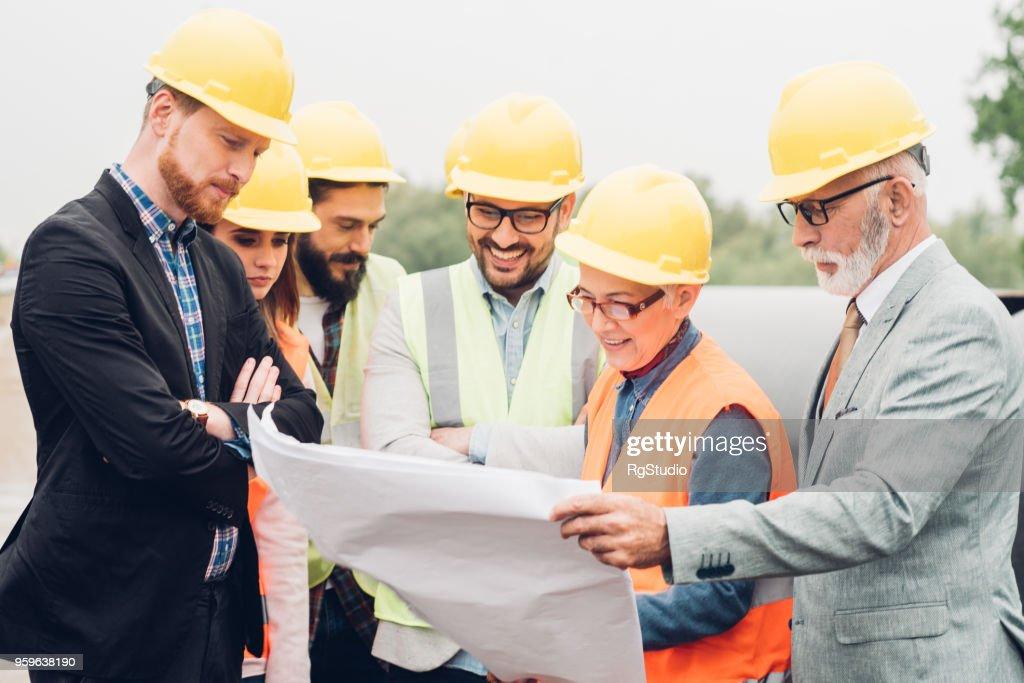 Multi-Geschlecht Bauarbeiter Überarbeitung der Baupläne : Stock-Foto