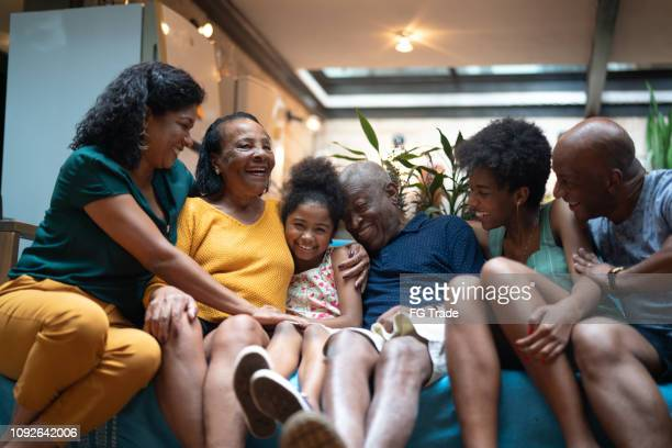 multi-generation african hispanic family at home - candid stock pictures, royalty-free photos & images
