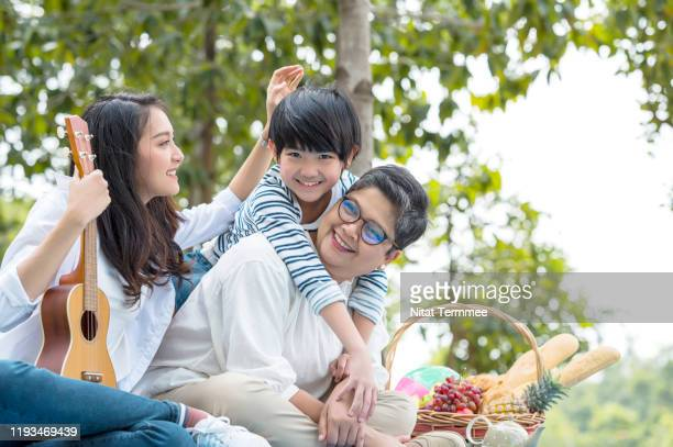 multi-generation asian family having fun together in the public park. - musical equipment stock pictures, royalty-free photos & images