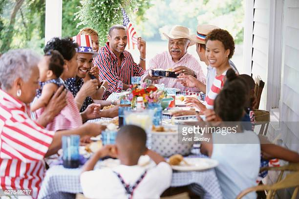 Multi-generation Black family eating at Fourth of July barbecue