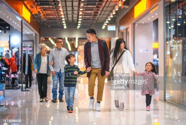 multi-generation chinese family enjoying evening at the mall - shopping centre stock pictures, royalty-free photos & images