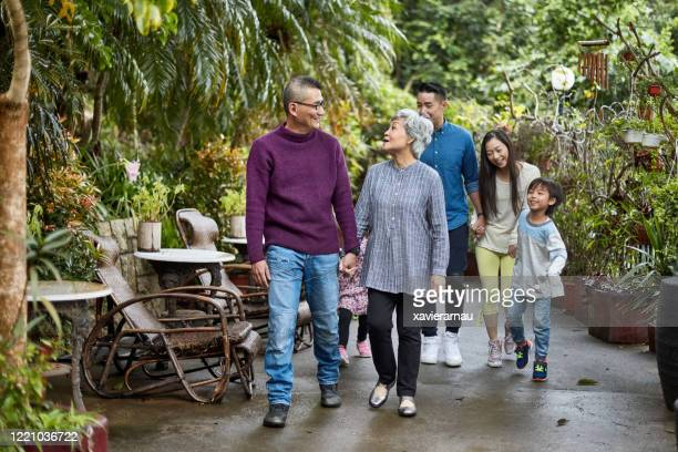 multi-generation chinese family enjoying outdoor walk - approaching stock pictures, royalty-free photos & images