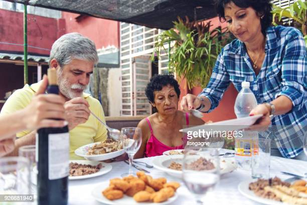 Multi-generation Cuban Family having dinner outdoors