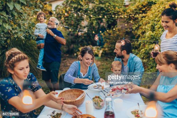 multi-generation family at a dinner party - generational family stock photos and pictures