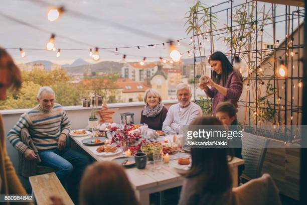 multi-generation family at a dinner party - balcony stock pictures, royalty-free photos & images