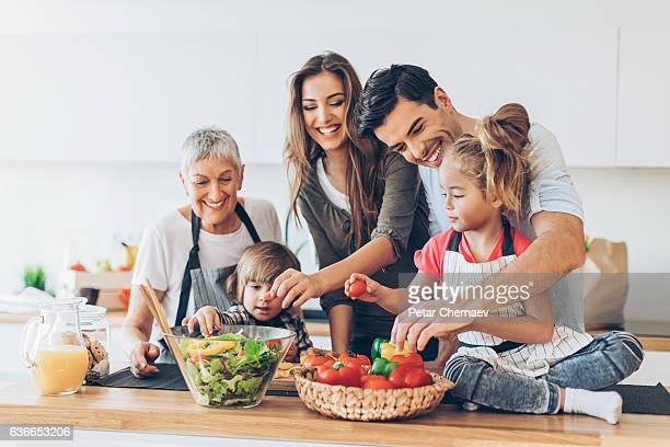 multi-generation family cooking - vegetarian food stock pictures, royalty-free photos & images