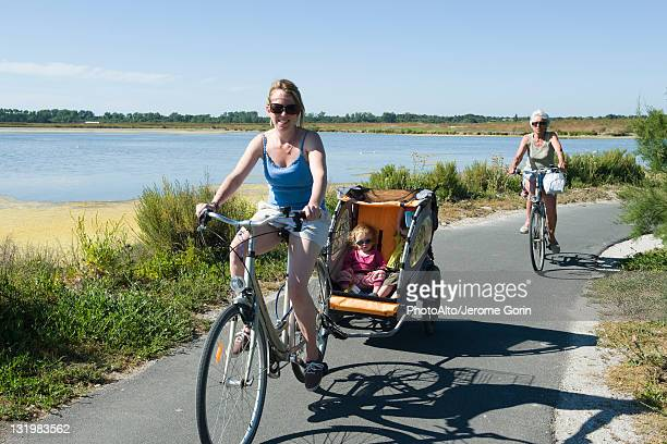 Multi-generation family enjoying bicycle ride, children sitting in bicycle trailer