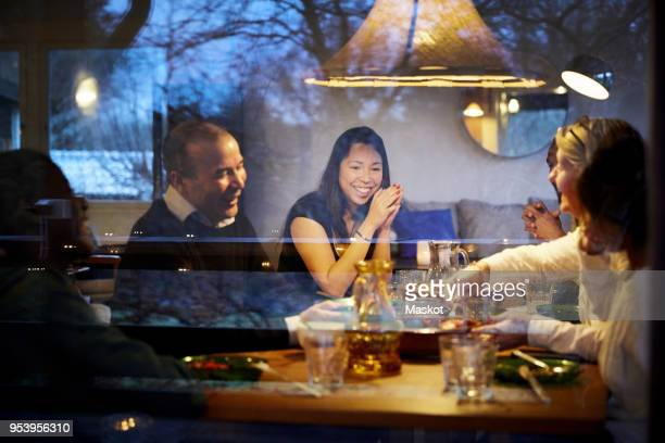 multi-generation family enjoying dinner at table seen through glass window - photographed through window stock pictures, royalty-free photos & images