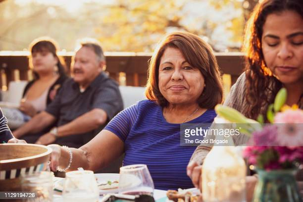multi-generation family enjoying outdoor dinner party - man eating woman out stock photos and pictures
