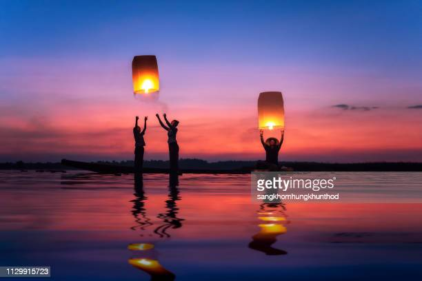 multi-generation family flying sky lanterns on mekong river at sunset, thailand - releasing stock photos and pictures