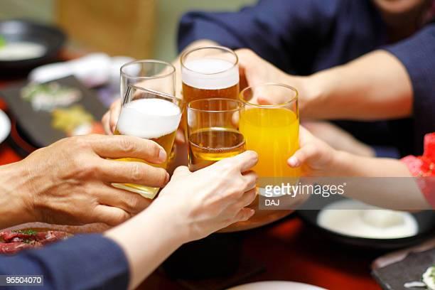 Multi-generation family having dinner, toasting with glasses
