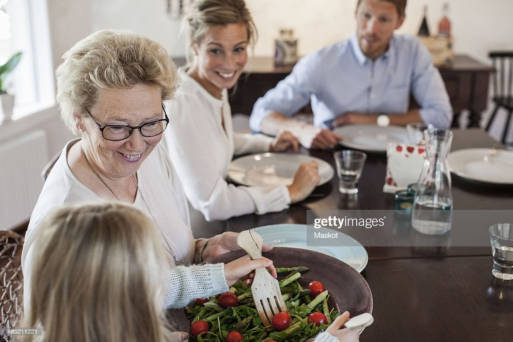 Multi-generation family having lunch at dining table : Stock Photo