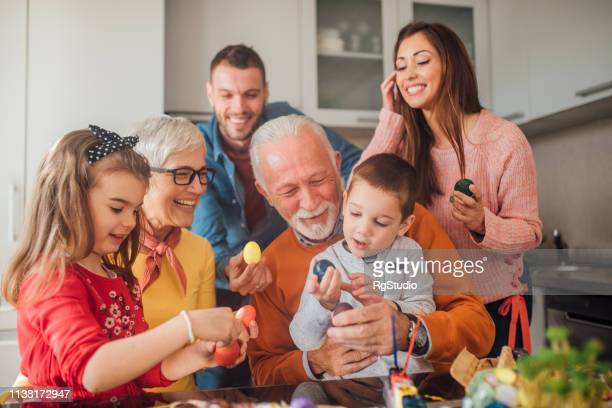 multi-generation family holding easter eggs and smiling - pasqua foto e immagini stock