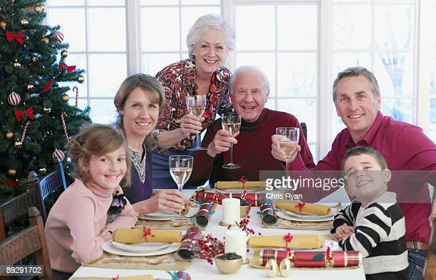 Multi-generation family holding wine glasses at Christmas dinner