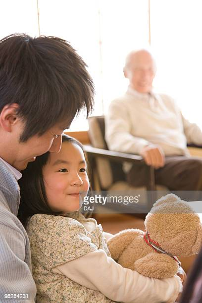 Multi-generation family in the inn, girl holding a teddy bear, differential focus