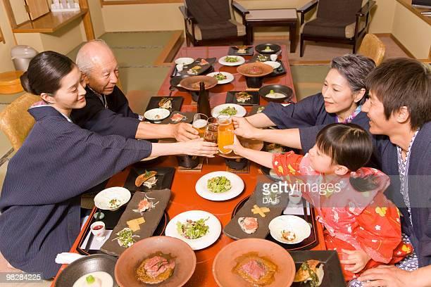 Multi-generation family in Yukata having dinner, toasting with glasses