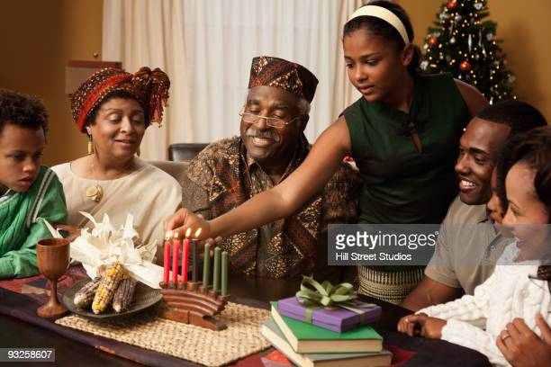 Multi-generation family lighting Kwanzaa candles
