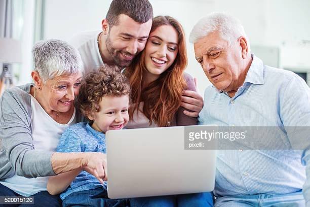 Multi-generation family looking at a laptop
