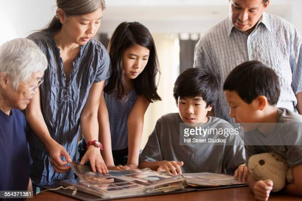multi-generation family looking at photo album - childhood photo album stock photos and pictures