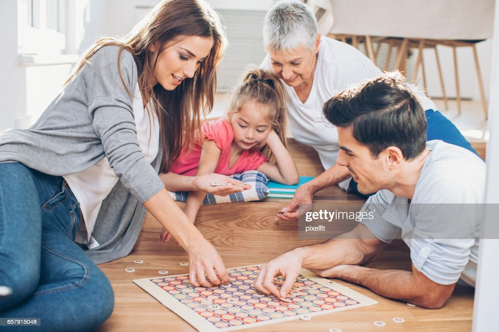 Multi-generation family playing a board game : Stock Photo
