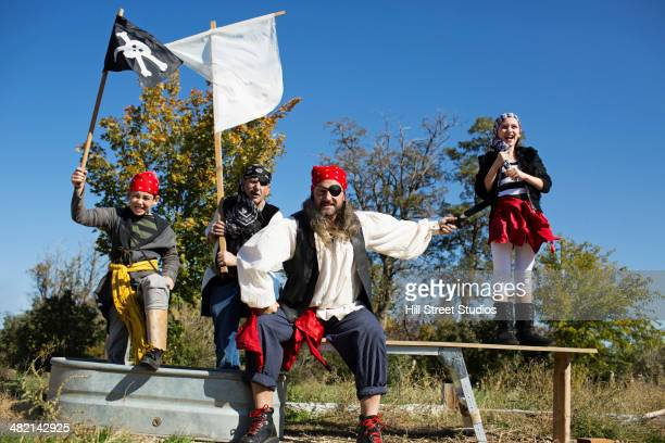 Multi-generation family playing in pirate costumes outdoors