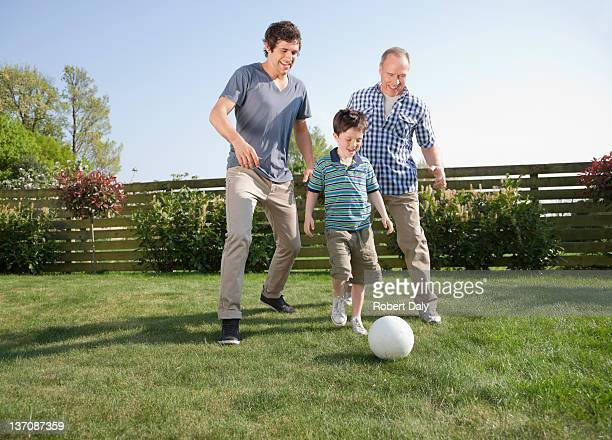 Multi-generation family playing soccer in backyard