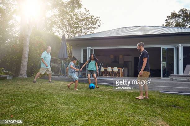 multi-generation family playing soccer on lawn - domestic garden stock pictures, royalty-free photos & images