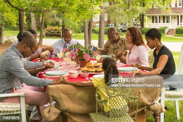 Multi-generation family praying at picnic table
