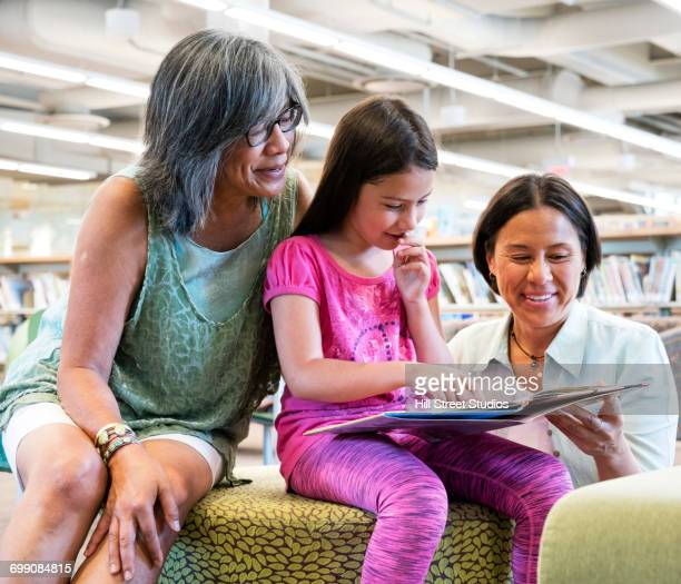 multi-generation family reading book in library - philippines family stock pictures, royalty-free photos & images