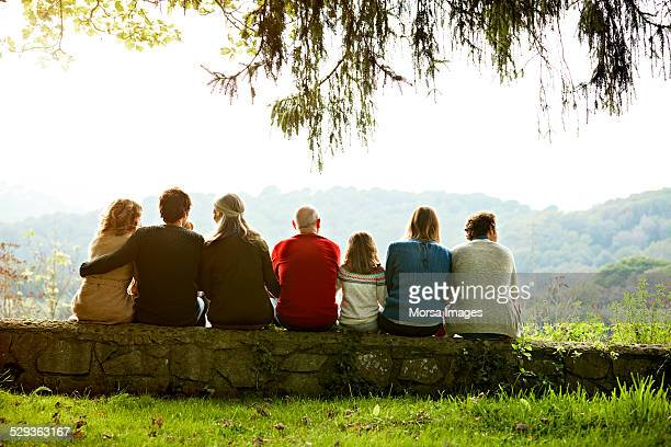 multi-generation family relaxing on retaining wall - generational family stock photos and pictures
