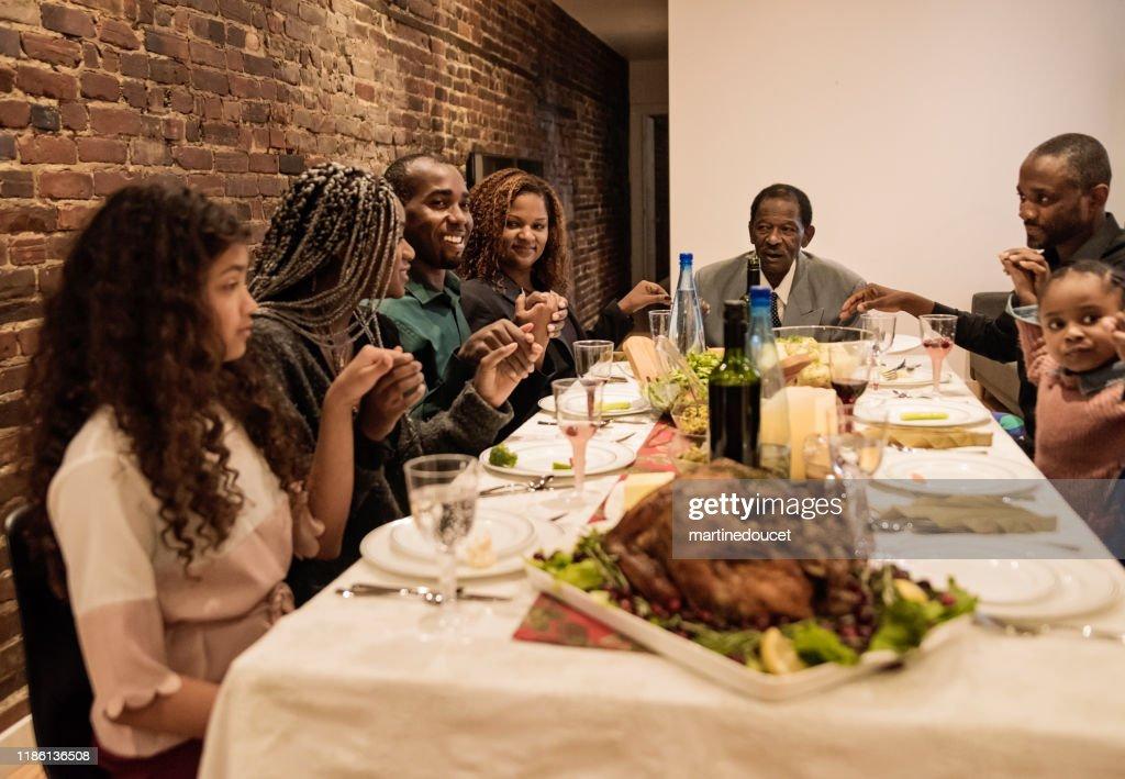Multi-generation family saying grace for Thanksgiving dinner. : Stock Photo