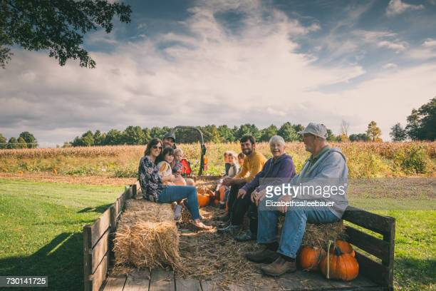 Multi-generation family sitting in a wagon at a pumpkin patch