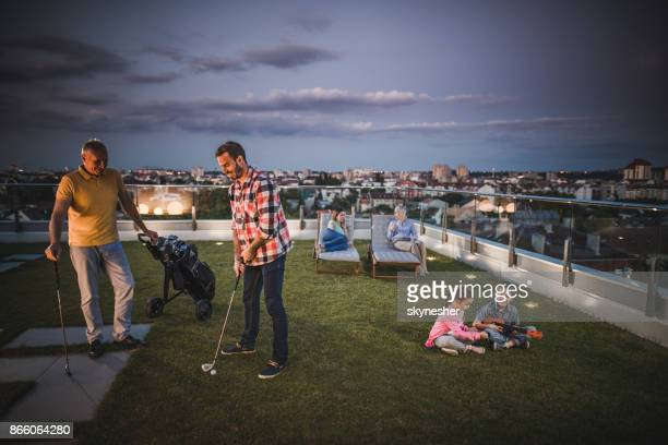 multi-generation family spending an evening on a penthouse terrace. - penthouse girls stock pictures, royalty-free photos & images