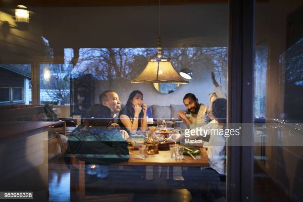 multi-generation family talking while having dinner at table seen through window - photographed through window stock pictures, royalty-free photos & images