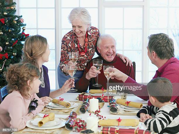 multi-generation family toasting at christmas dinner - celebratory toast stock pictures, royalty-free photos & images