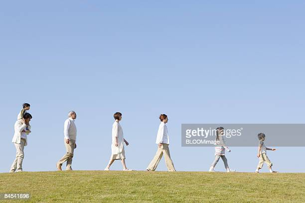 Multi-generation family walking in line, side view