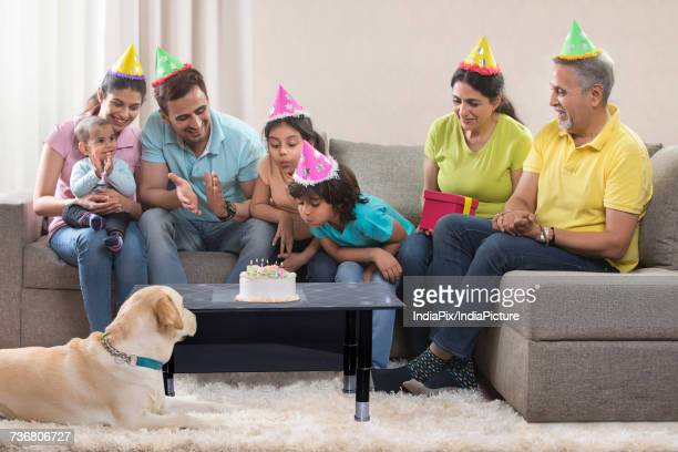 Multi-generation family with dog celebrating birthday party