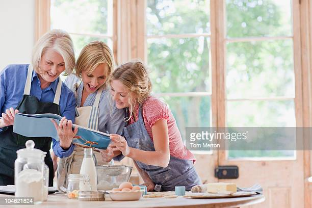 multi-generation females looking at cookbook and baking in kitchen - magazine stock pictures, royalty-free photos & images